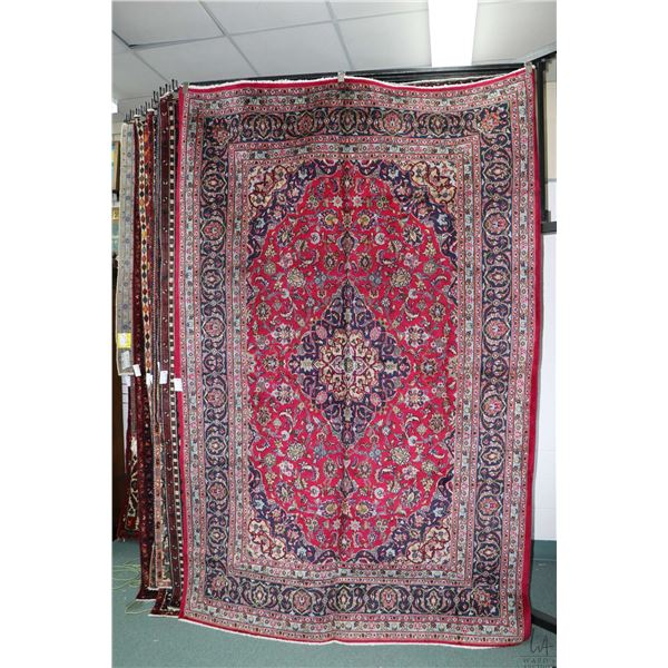 100% Iranian Mashad wool area carpet with floral medallion and overall floral design, red background