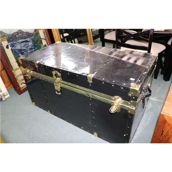 Semi contemporary metal bound steamer trunk with black finish and faux brass accents, has had pad lo
