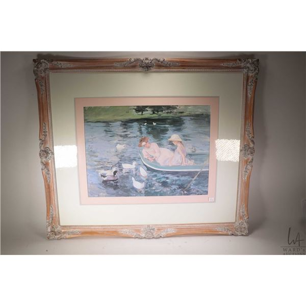 Large framed print of a Claude Monet painting featuring mother and child in a boat with ducks, overa