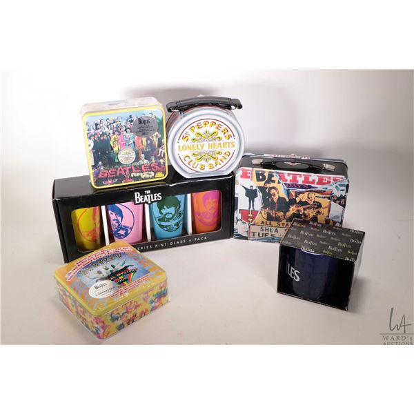 Selection of Beatles merchandise including two lunch boxes, two sealed puzzles, a four pack of pint
