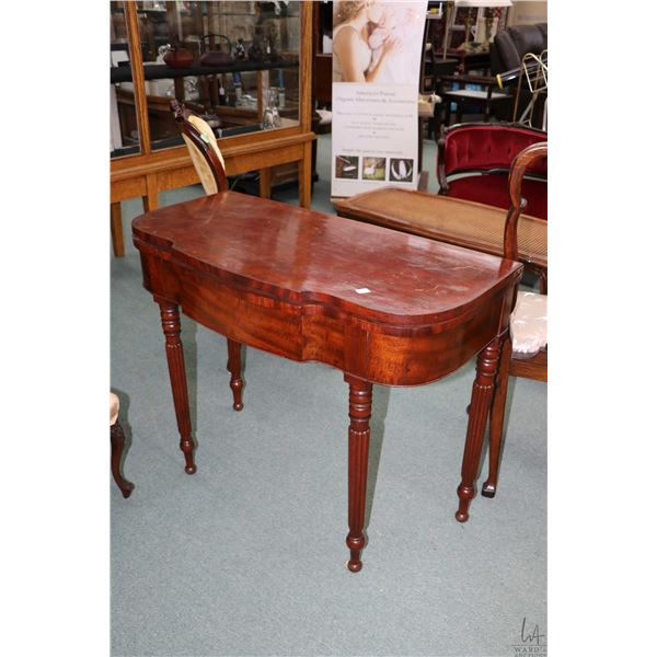 Antique 19th century mahogany fold over tea table on tall reeded support, one of which pulls out for