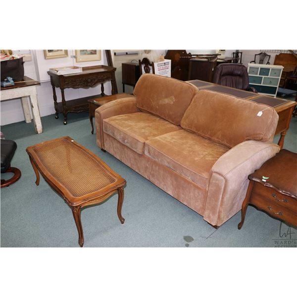 Faux suede two seat hide-a-bed and a French provincial coffee table with rattan insert, missing glas