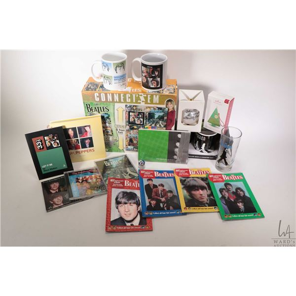 Selection of Beatles collectibles including cups, Christmas tree ornament, pocket books and Beatles