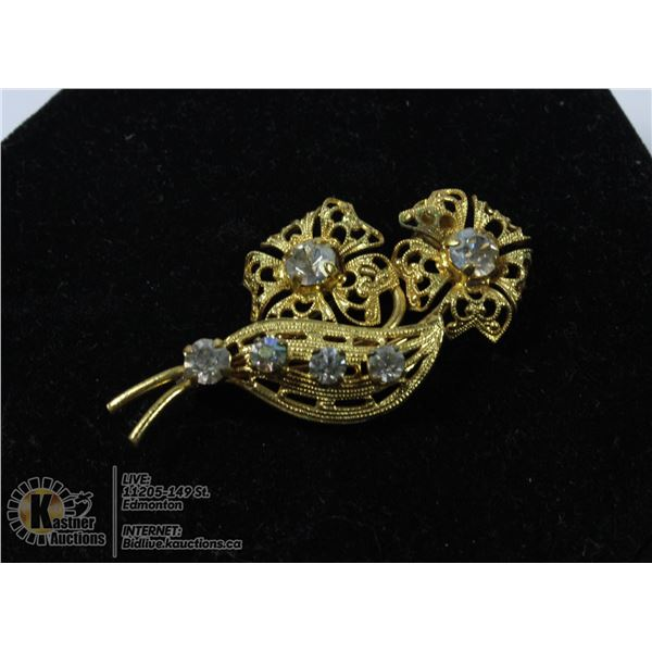 A 1950S GOLD TONE FLOWER BROOCH WITH CLEAR