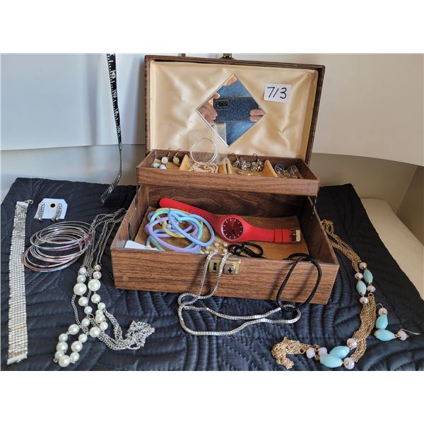 Vintage jewelry box filled with costume pieces.