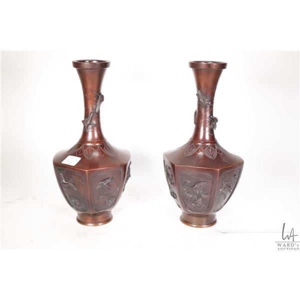 Pair of antique Meiji period Japanese bronze vases with high relief birds and foliage in six panels,