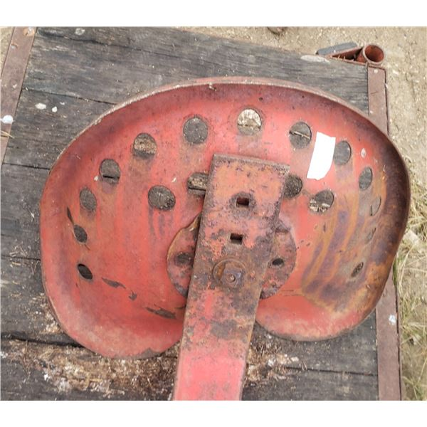 very old tractor seat with bracket attached