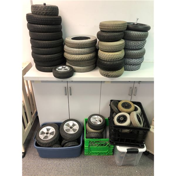 Large group of assorted power mobility scooter wheels