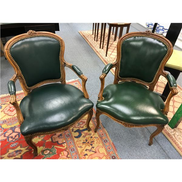 Pair of early 1900's green leather upholstered mahogany arm chairs