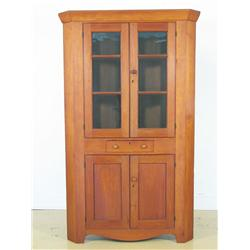 A 19th Century American maple and walnut corner cabinet.