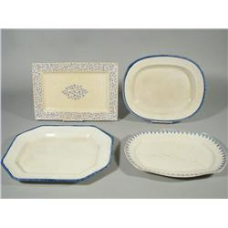A group of four blue and white ironstone platters.