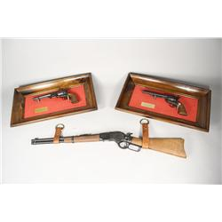 A collection of three mounted model guns.