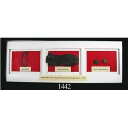 Framed set of artifacts (buckle, shoe sole and buttons).