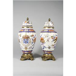 A pair of French porcelain lidded urns mounted on gilt brass feet