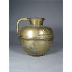 A Persian Hammered Brass Pitcher.
