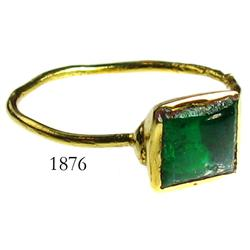 Gold ring with green gemstone (possibly an emerald).