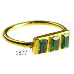Gold ring with 3 small green gemstones (possibly emeralds).