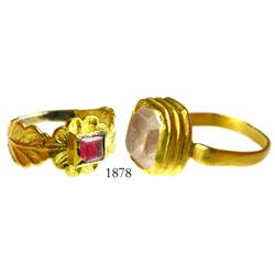 Lot of 2 gold rings (one broken) with crystal stones (one colored red, the other clear).