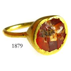 Gold ring with red-orange stone.