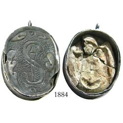 Silver reliquary pendant with clay Madonna figure inside.