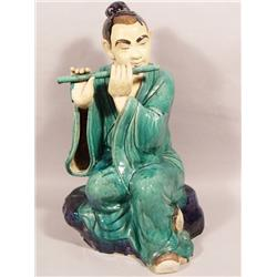 A Chinese Earthenware Figure of a Boy Playing the Flute.