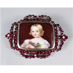 A Garnet and Porcelain Brooch.