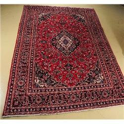 A Persian Mashad Wool Rug.