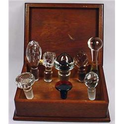LOT OF VINTAGE GLASS STOPPERS IN A WOODEN BOX