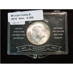 298. 1964 D Kennedy Half Dollar. Gem BU. Mounted in a special plastic memorial case.