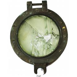 Large brass porthole, intact but glass inside shattered.