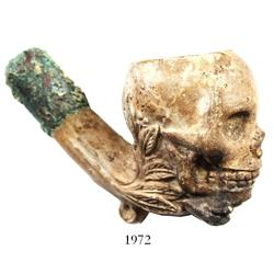 Ornate, skull-shaped clay pipe with cuprous stem.