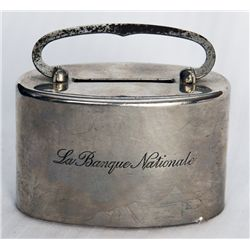 LA BANQUE NATIONALE, engraved on side of bank. An oval satchel bank. Coin slot on top. Handle at top