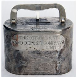 THE OTTAWA TRUST AND DEPOSIT COMPANY LIMITED. An oval steel satchel bank. Coin slot on top. Handle a