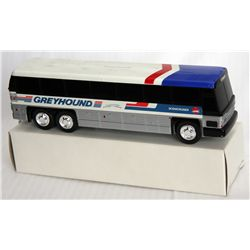 GREYHOUND BUS. Coin slot on top. Red, White and Blue plastic. New, in box of issue.