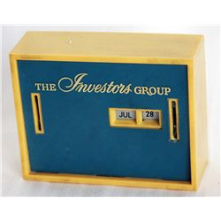 THE INVESTORS GROUP. A rectangular Coin Calendar bank. Two coin slots on front. Currency slot on bac