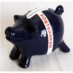 POSTIPAUKKI. Piggy Bank shaped. Black plastic with a white band. Coin slot on top. 6cm x 7cm x 10cm.