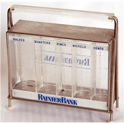 RAINIER BANK. Rectangular clear plastic bank with blue highlights. No key. Five coins slots along fr