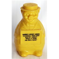 SURREY CREDIT UNION. A yellow plastic bank in the shape of a standing pig. Coin slot on top of back.