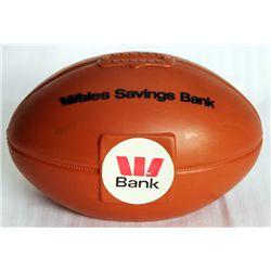 WALES SAVINGS BANK. A Football shaped, tan plastic bank. Coin slot on top. 9cm x 9cm x 14cm. EF.