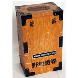 NOMURA SECURITIES CO., LTD. A RECTANGULAR Wood box bank, with black metal at the corners. Coin slot