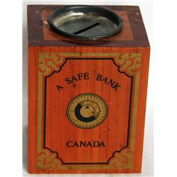 A SAFE BANK'/CANADA. A rectangular shape wood bank. Decals of a safe and dial on front. Coin slot on