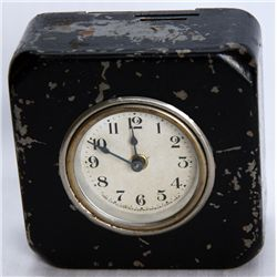 A rectangular shaped Clock Bank. Two coin slots on top. 9 1/2cm x 4cm x 9 1/2cm. Steel, with a black