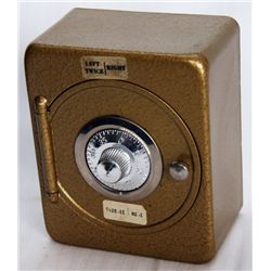 A Safe or Vault shaped bank. Coin slot on back. 10cm x 6cm x 12cm high. Steel, with a gold finish, a